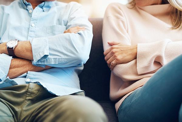 Dwójka ludzi siedzi zzałożonymi rękami